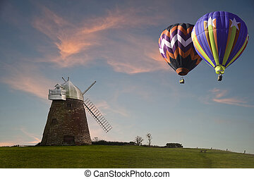 Traditional old windmill at sunset with hot air balloons