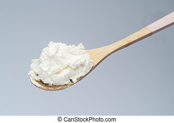 Traditional organic Mascarpone cheese in wooden spoon on grey background