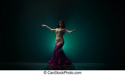 Traditional oriental belly dancer girl dancing on smoke...