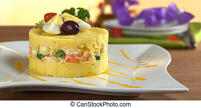 Traditional Peruvian dish called Causa made of mashed yellow and white potato mixed with aji (hot pepper) and lime juice and filled with vegetables (corn, peas, carrots) and mayonnaise and garnished with eggs and olives (Selective Focus, Focus on the front)