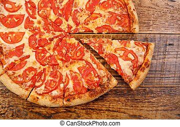 Traditional Pizza Margherita on a wooden background. Close-up. The concept of delicious food.