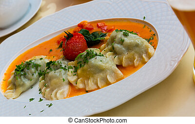 Traditional polish dumplings with mashed potato and tomato at plate