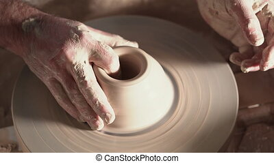 Traditional pottery making, man teacher shows the basics of pottery in art studio. Artist operates hands, which gently creating correctly shaped handmade from clay.