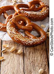Traditional pretzel with salt and pistachio close-up. Vertical