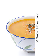 Traditional pumpkin soup with ingredients isolated on white
