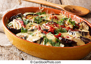 Traditional recipe for baked eggplants with tomatoes, herbs and cheese close-up. horizontal