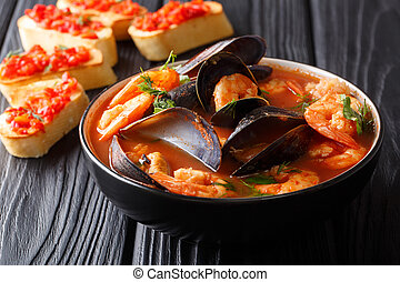 Traditional recipe for French bouillabaisse soup with seafood and fish close-up in a bowl served with toasts. horizontal