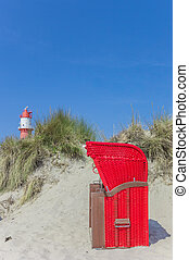 Traditional red beach chair in the dunes of Borkum