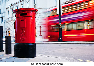 Traditional red mail letter box and red bus in motion in...