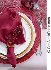 Traditional red theme festive table place setting.