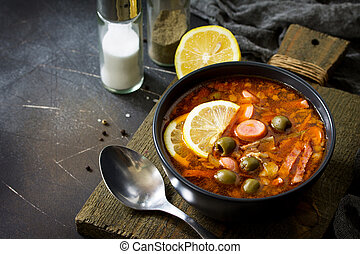 Traditional Russian soup Solyanka with meat, sausages, vegetables, capers, pickles and olives with lemon on black background. Rustic style. Free space for your text.