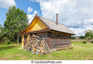 Traditional russian wooden bath at the bank of lake in summer sunny day