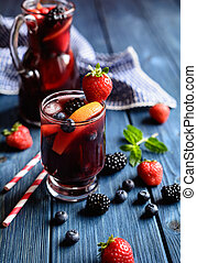 Traditional Sangria drink with red wine, tropical fruit and berries in a glass jar
