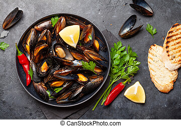Traditional seafood mussels in wine sauce and baguette ...
