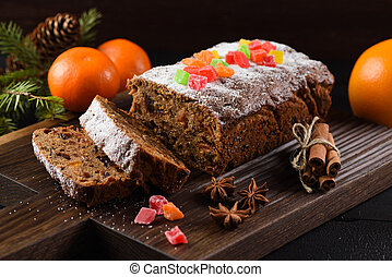 Traditional sliced freshly baked fruit cake decorated with candied fruits, star anise, cinnamon and clementines on dark background