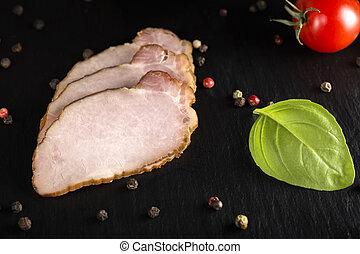 Traditional slices of smoked pork on dark slate
