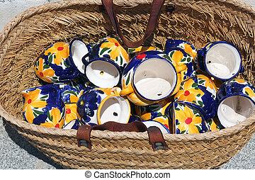 traditional spanish ceramic jugs in rattan basket