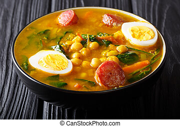 Traditional Spanish chickpeas with spinach, sausages chorizo, boiled eggs close-up in a bowl. horizontal