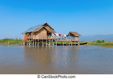 Traditional stilts house in water under blue sky - ...