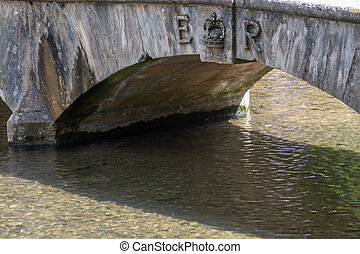 Traditional stone bridge over stream with Queens Coronation logo