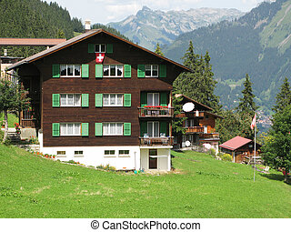 Traditional Swiss cottage against Eiger mountain in Jungfrau...