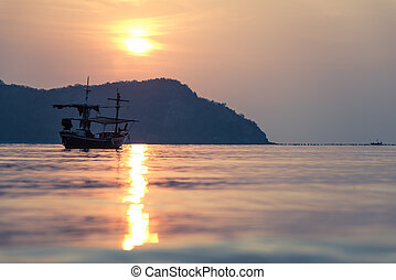 Traditional thai boat at sunset on sea in Thailand