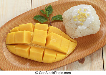 Traditional Thai dessert of mango with sticky rice mix...