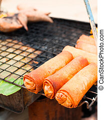 Traditional Thai food at market. Spring rolls on grill
