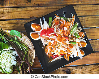 """Traditional thai food, Papaya salad with salted egg or what we call """" Somtum Thai"""" in Thai with ingredients. Placed in a black dish and with fresh vegetables on the side On the wood background."""