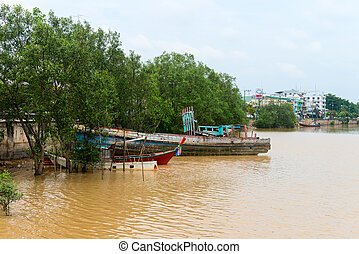 Traditional timber fishing boat abandoned outdoors on a river bank