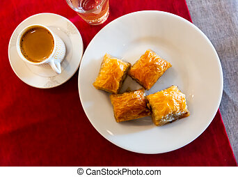 Traditional Turkish dessert - baklava on a plate and cup of coffee