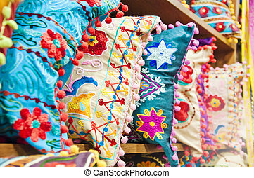 Pillows with traditional Turkish designs on the shelves of a bazaar store in Istanbul
