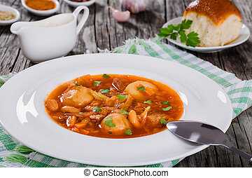 Traditional Ukrainian or Russian vegetable soup, borscht cooked in meat broth with new potatoes  in white wide rim dish. sour cream in gravy boat and bun sprinkled with garlic on background, close-up