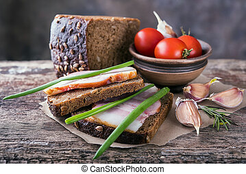 Traditional ukrainian sandwiches with brown rye bread, smoked lard, green onions.