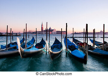 Traditional Venetian gondolas moored on the waterfront of Venice, Italy.