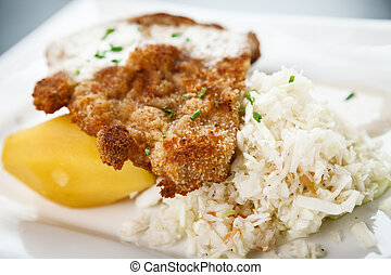 Traditional viennese Schnitzel with potato salad and rice on...