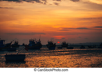 traditional Vietnamese fishing boats on the sea in the background of sunset