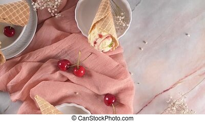 Traditional waffle cones with ice cream and cherry fruits on...