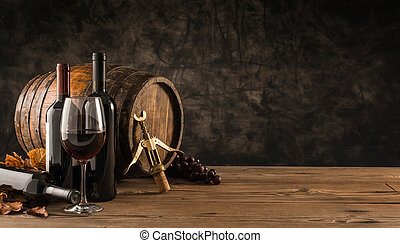 Wine glass, wooden barrel and collection of excellent red wine bottles in the cellar: traditional winemaking and wine tasting concept