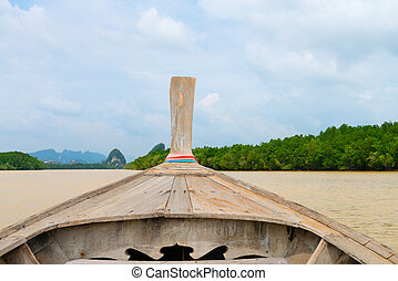 Traditional wooden boat against tropical background