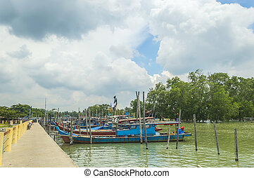 Traditional wooden boat at jetty with blue skies