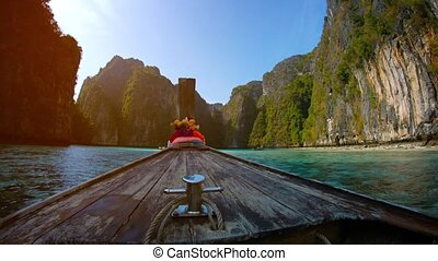 """Traditional wooden boat floats between the limestone rocks...."