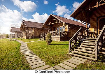 wooden cottages at sunny day in the countryside