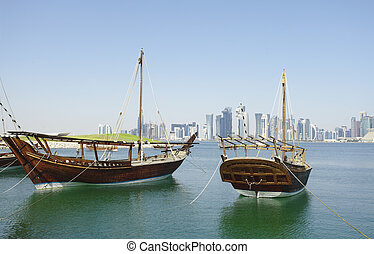Traditional wooden dhows and Doha skyline - Traditional...