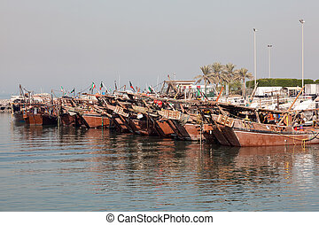 Traditional wooden dhows in the fishing port of Kuwait, ...