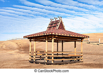 Traditional wooden gazebo in the Buryat-style on the shore...