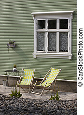 Traditional wooden icelandic facade with deckchairs in ...