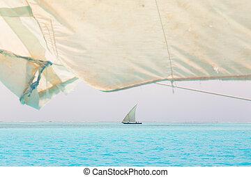 Traditional wooden sailboat sailing on a horizon of turquoise blue sea of Zanzibar, Tanzania, Afrika.