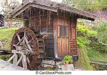 Traditional wooden water wheel spinning at Tsumago - juku in Tsumago