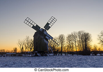 Traditional wooden windmill by sunset in winter season